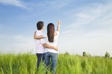 man looking at sky: young couple in meadow with hand in air, hugging. Copy space