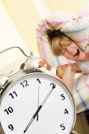 Close up of alarm clock. Young woman in the background covering ears with pillow. Stock Photo - 3133822