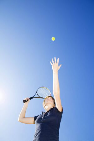 blond woman playing tennis, about to hit the ball. Copy space photo