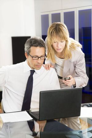 Businesspeople looking at laptop in office. photo