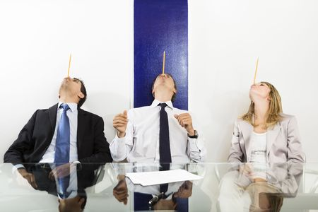 Businesspeople balancing pencils on face in meeting room.