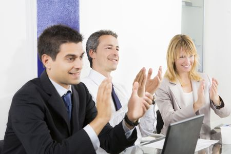 Businesspeople clapping in business meeting. photo
