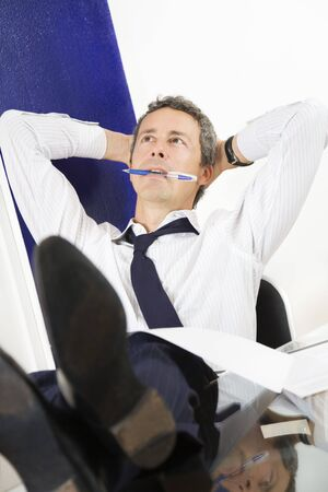 Mature businessman relaxing in office, leaning feet on desk photo