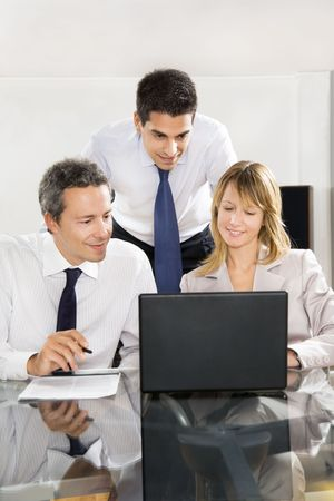 sala de reuniões: Businesspeople looking at laptop in meeting room.