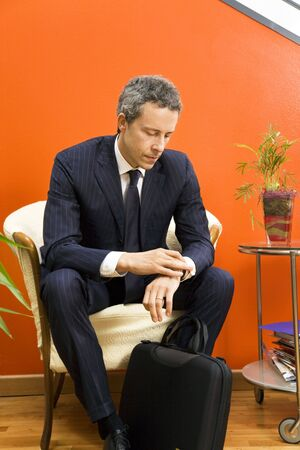 Businessman checking his watch while waiting