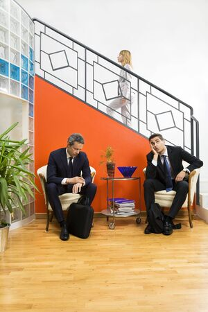 Businessmen waiting in office. Woman stepping up the staircase Stock Photo
