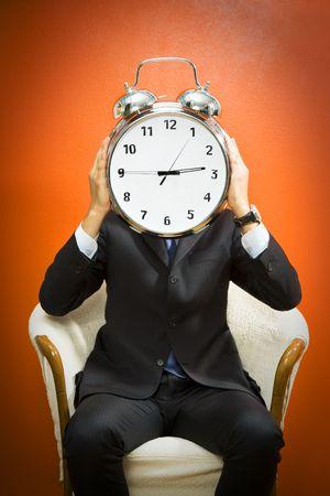 Businessman with alarm clock on head, studio shot. Stock Photo - 3175725
