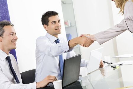 Businessman and woman shaking hands in office with colleague watching. photo