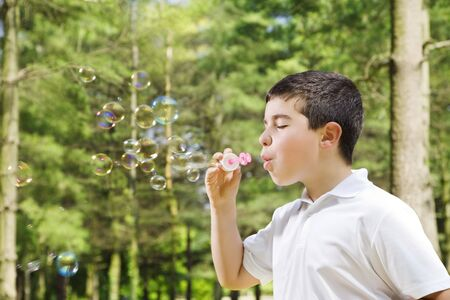 Young boy blowing bubbles in park. Copy space photo
