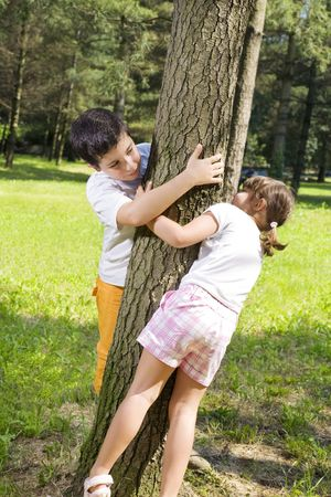 hide and seek: Portrait of young happy boy and girl playing hide and seek at park. Stock Photo