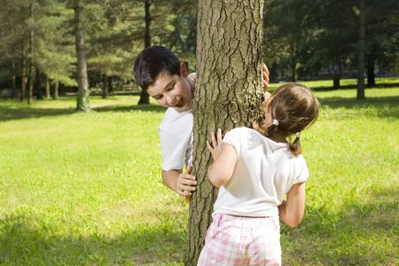 italian ethnicity: Portrait of young happy boy and girl playing hide and seek at park. Stock Photo