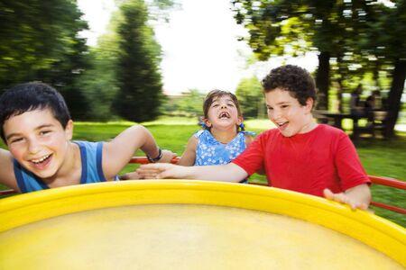 trois enfants: Trois enfants sur la filature merry go round Banque d'images