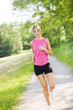 Young blond woman jogging on pathway in park photo