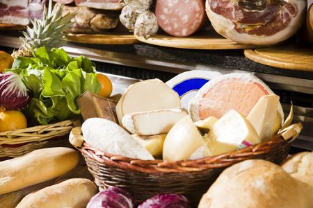 Assortment of cheeses in basket, meats and breads