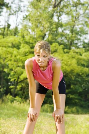 Young blond woman taking breath after jogging photo