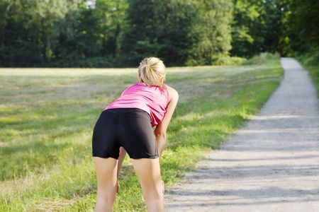 bend over: Rear view of young woman resting on pathway. Copy space