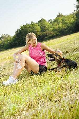 petting: Young woman with dog relaxing in park