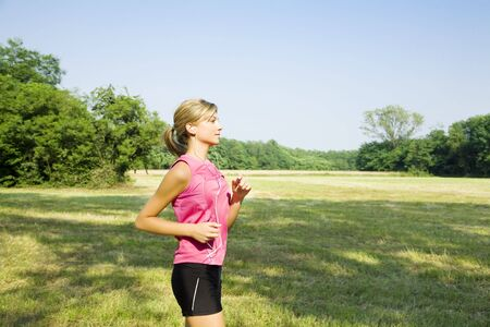 Young blond woman jogging on pathway in park, listening to music photo