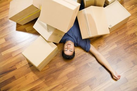 High angle view of young man sleeping underneath moving boxes photo