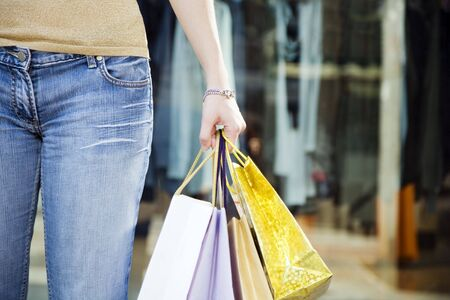 Cropped view of woman holding shopping bags photo