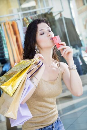 shopping scene: Mid adult Italian woman holding shopping bags and kissing credit card