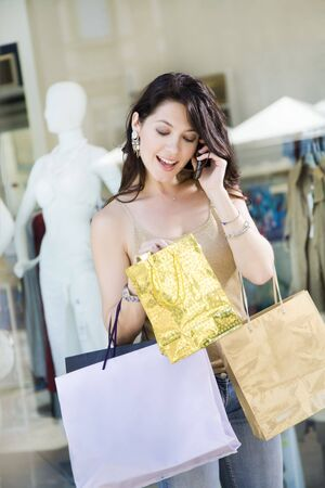 Mid adult Italian woman on the phone and holding shopping bags photo