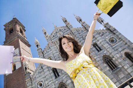 milánó: Low angle view of mid adult Italian woman holding shopping bags in front of cathedral