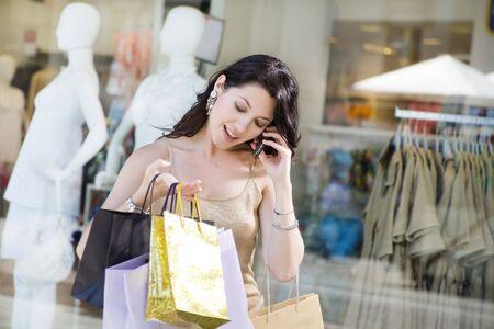 mil�n: Mediados de adultos mujer italiana en el tel�fono y la celebraci�n de bolsas de la compra