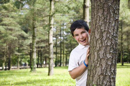Portrait of young happy boy behind tree at park. Stock Photo - 3425719