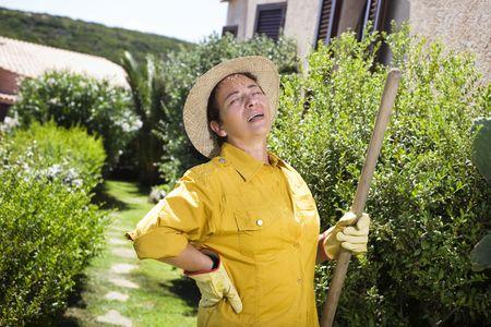 dolor muscular: �Cansado de alto nivel mujer italiana tener dolor de espalda, mientras que la jardiner�a  Foto de archivo