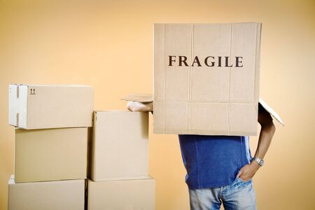 Man with fragile box covering head, studio shot Stock Photo - 3477375