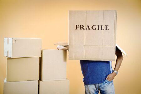 Man with fragile box covering head, studio shot Stock Photo - 3477375