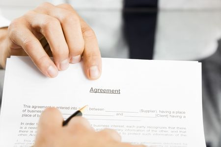Businessman holding agreement for signature. Close up photo