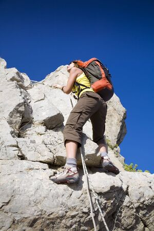 young woman reaching the top of a mountain. Copy space photo