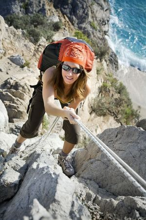 young woman reaching the top of a mountain.  Stock Photo
