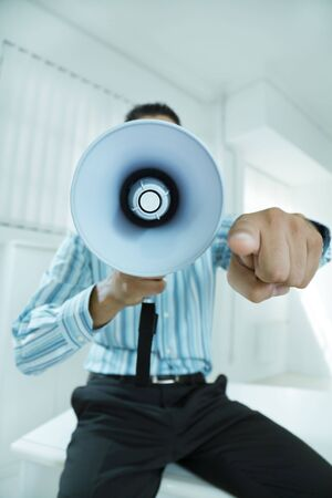 young businessman in office screaming on the megaphone photo