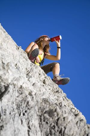 young woman drinking from flask on top of the mountain photo