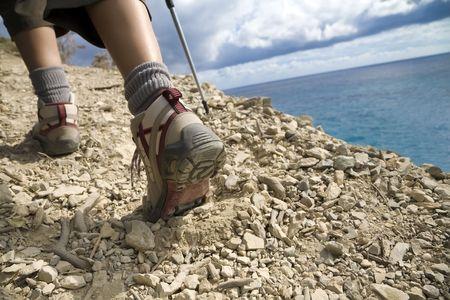 登る: 若い女性は海の近くの崖の上のハイキング 写真素材