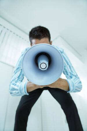 young businessman in office talking on the megaphone photo