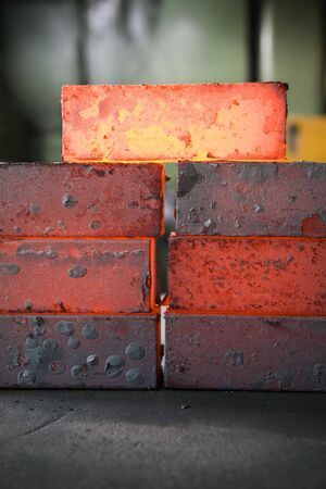 ironwork: piles of hot iron blocks in foundry. Narrow focus on central block Stock Photo