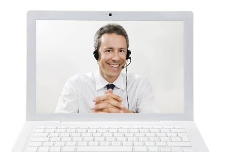 telephone headsets: Mid adult businessman wearing headset on screen of laptop computer  Stock Photo