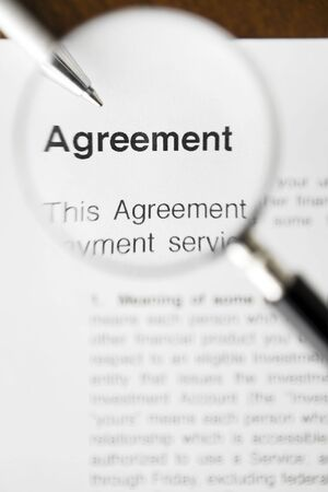 Magnifying glass over agreement paperwork and pen  Stock Photo