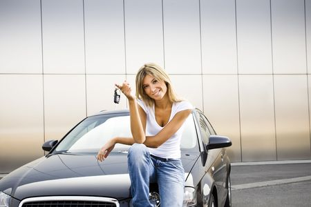 rent a car: Young woman holding keys to new car