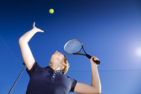 jugando tenis: mujer rubia jugar al tenis, a punto de golpear la bola. Copiar el espacio