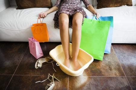 Vrouw uitzettijd voeten in het water na een lange dag winkelen Stockfoto