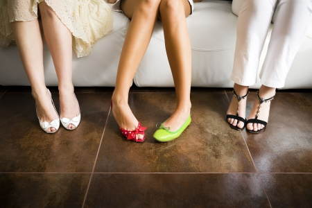 high heel shoes: Cropped view of woman wearing mismatched shoes with women in high heels sitting beside