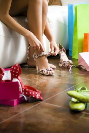 Mujer joven tratando de zapatos de tacón alto
