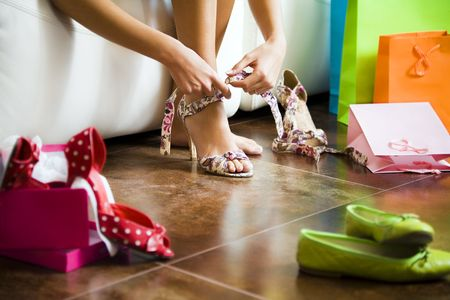 high fashion: Young woman trying on high heel shoes