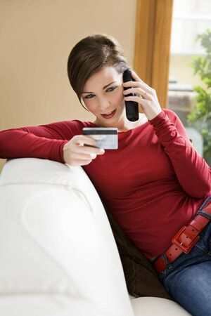 Young woman relaxing at home on the phone with credit card Stock Photo - 3826304