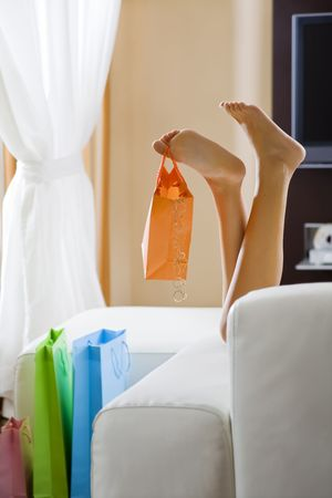 Young womans legs dangling shopping bag  photo